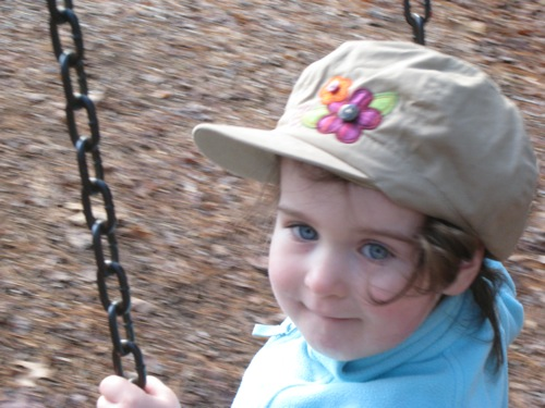 Phoebe in a flowered cap, age 2 and a half.
