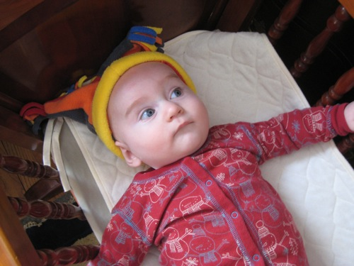 Theo in the cradle, wearing a funky hat. (Age 4 months)