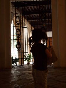 Phoebe peers through a gate at Alcazar in Sevilla.